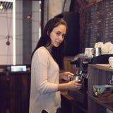 Concetto di affari del caffè - barista di signora del primo piano in latte preparante e di versamento del grembiule fotografie stock