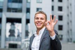 Concetto di affari, della gente, di visione e di successo - l'uomo d'affari sorridente felice in occhiali ed il vestito che mostr Fotografia Stock