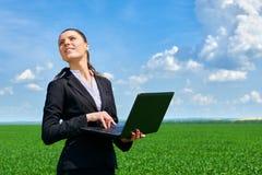 Concetto di affari - donna nel lavoro all'aperto del campo di erba verde sul computer portatile Ragazza vestita in vestito nero B Immagine Stock