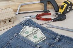 Concetto di affari e della costruzione Attrezzi differenti, dollari nella tasca dei jeans su fondo di legno Fotografie Stock Libere da Diritti