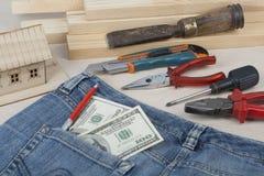 Concetto di affari e della costruzione Casa di modello e attrezzi differenti, dollari nella tasca dei jeans su di legno Fotografia Stock