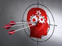 Concetto di affari: frecce in testa con l'obiettivo degli ingranaggi sulla parete Immagine Stock