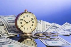 Concetto di affari Il tempo è denaro Orologio d'annata vicino ai contanti americani del dollaro e monete con il fondo blu piacevo Immagine Stock Libera da Diritti