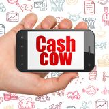Concetto di affari: Mano che tiene Smartphone con il cash cow su esposizione Immagini Stock