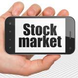 Concetto di affari: Passi la tenuta dello Smartphone con il mercato azionario su esposizione Fotografia Stock Libera da Diritti