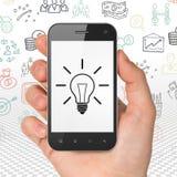 Concetto di affari: passi lo smartphone della tenuta con la lampadina su esposizione Fotografie Stock Libere da Diritti