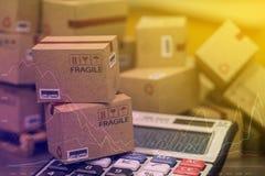 Concetto di affari: Piccoli scatole di cartone e calcolatore Concetto immagini stock