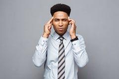 Concetto di affari - ritratto dell'uomo afroamericano sollecitato frustrato di affari su fondo grigio Immagine Stock
