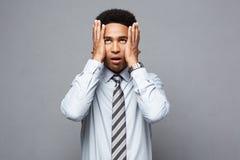Concetto di affari - ritratto dell'uomo afroamericano sollecitato frustrato di affari su fondo grigio Immagini Stock Libere da Diritti