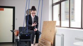 Concetto di affari Una donna che si siede sulle oscillazioni nell'ufficio e che esamina il suo telefono immagine stock libera da diritti