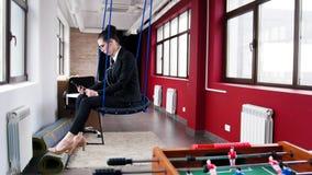 Concetto di affari Una donna che si siede sulle oscillazioni nell'ufficio ed ascoltare la musica fotografia stock