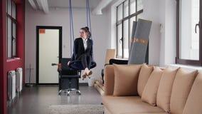 Concetto di affari Una donna che si siede sulle oscillazioni nell'ufficio fotografia stock