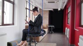 Concetto di affari Una donna in vetri che si siedono sulle oscillazioni nell'ufficio ed ascoltare la musica fotografia stock libera da diritti