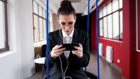 Concetto di affari Una giovane donna in vetri che si siedono sulle oscillazioni nell'ufficio, ascolta la musica ed esaminando immagini stock libere da diritti