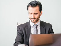 Concetto di affari - uomo stressante bello di affari del ritratto nella scossa del vestito che esamina lavoro in computer portati Immagine Stock Libera da Diritti