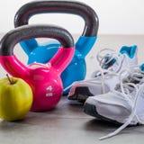 Concetto di allenamento sul pavimento grigio con le scarpe da tennis e le campane del bollitore Fotografia Stock