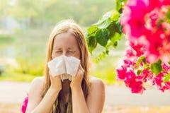 Concetto di allergia del polline La giovane donna sta andando starnutire Alberi di fioritura nel fondo fotografia stock