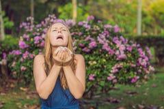Concetto di allergia del polline La giovane donna sta andando starnutire Flowerin fotografia stock