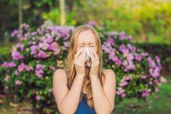 Concetto di allergia del polline La giovane donna sta andando starnutire Flowerin Fotografia Stock Libera da Diritti