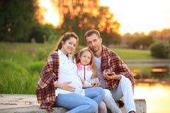Concetto di allevare i bambini - una famiglia felice avvolta in un blanke Fotografie Stock