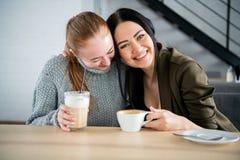 Concetto di amicizia e di comunicazione - giovani donne sorridenti con le tazze di caffè al caffè immagine stock libera da diritti
