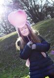 Concetto di amore: bambino che tiene un baloon in forma di cuore su un bastone Immagine Stock