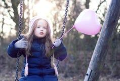 Concetto di amore: bambino su un'oscillazione che tiene un baloon in forma di cuore Fotografie Stock