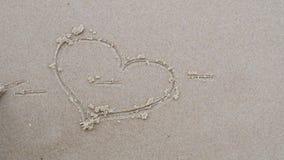 Concetto di amore Disegno del cuore sul primo piano della sabbia di mare video d archivio