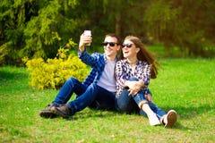 Concetto di amore, di tecnologia, di relazione, della famiglia e della gente - giovane coppia sorridente felice che prende selfie fotografie stock libere da diritti