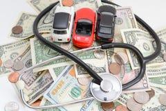 Concetto di analisi di industria automobilistica con le automobili e lo stetoscopio del giocattolo su soldi Immagini Stock Libere da Diritti