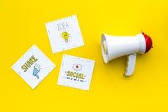 Concetto di annunci di media di Socail Megafono vicino alle icone sociali di media sulla vista superiore del fondo giallo fotografia stock