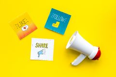 Concetto di annunci di media di Socail Megafono vicino alle icone sociali di media sulla vista superiore del fondo giallo fotografie stock