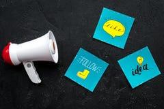 Concetto di annunci di media di Socail Megafono vicino alle icone sociali di media sulla vista superiore del fondo nero fotografia stock libera da diritti