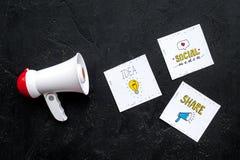 Concetto di annunci di media di Socail Megafono vicino alle icone sociali di media sulla vista superiore del fondo nero fotografia stock