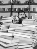 concetto di arresto di tempo Insegnante o studente con la barba che studia nella biblioteca Uomo, scienziato che dà una occhiata  Fotografia Stock Libera da Diritti