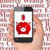 Concetto di attività bancarie: Passi la tenuta dello Smartphone con il salvadanaio con la moneta su esposizione Immagine Stock Libera da Diritti