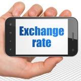 Concetto di attività bancarie: Passi la tenuta dello Smartphone con il tasso di cambio su esposizione Fotografia Stock