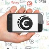 Concetto di attività bancarie: Passi la tenuta dello Smartphone con l'euro moneta su esposizione Immagine Stock Libera da Diritti