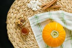 Concetto di autunno Piccoli zucca, semi, miele, noci e bastoni di cannella su un tovagliolo del cerchio del giacinto d'acqua sopr fotografia stock libera da diritti