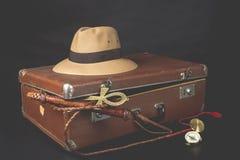Concetto di avventura e di viaggio Valigia marrone d'annata con la chiave del cappello, del bullwhip, della bussola e del ankh de Immagine Stock Libera da Diritti