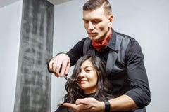 Concetto di bellezza, dell'acconciatura e della gente - giovane donna felice e parrucchiere che tagliano le punte dei capelli al  immagini stock libere da diritti
