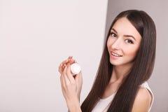 Concetto di bellezza, della gente, dello skincare e dei cosmetici - giovane donna felice con crema d'idratazione a disposizione e Fotografia Stock