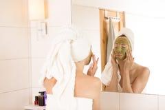 Concetto di bellezza La donna applica la maschera di protezione organica verde nel bagno Fotografie Stock