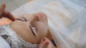 Concetto di bellezza Massaggi lo specialista che fa il massaggio di sollevamento della pelle al fronte del ` s del cliente al cen archivi video
