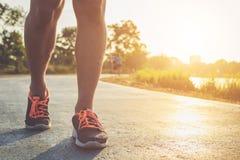 Concetto di benessere di allenamento dell'uomo: Piedi del corridore con il funzionamento della scarpa della scarpa da tennis Immagini Stock