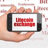 Concetto di Blockchain: Mano che tiene Smartphone con lo scambio di Litecoin su esposizione Fotografia Stock