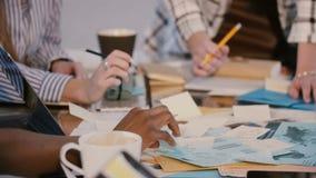 Concetto di 'brainstorming' e di lavoro di squadra, mani dei colleghi della società di affari che lavorano insieme, scriventi le video d archivio