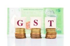 Concetto di buona e di servizi imposta di GST o con la pila di moneta e di valuta di ringgit della Malesia Immagini Stock