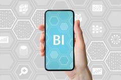 Concetto di business intelligence Passi la tenuta dello smartphone moderno davanti a fondo neutrale con le icone fotografie stock libere da diritti