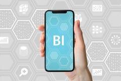 Concetto di business intelligence Passi la tenuta dello smartphone moderno davanti a fondo neutrale con le icone fotografie stock